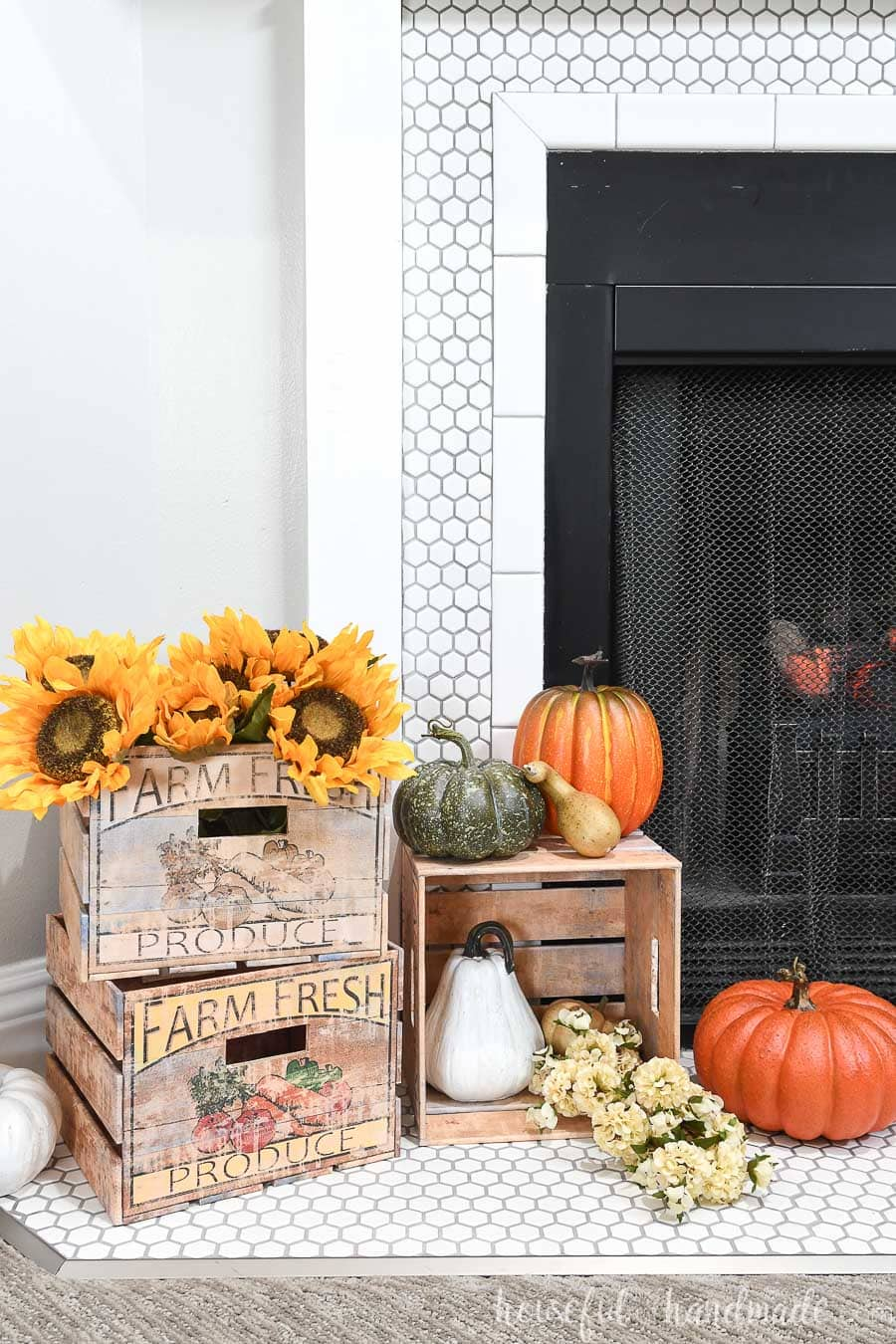 DIY decorative crates on the hearth of a fireplace decorated for fall.