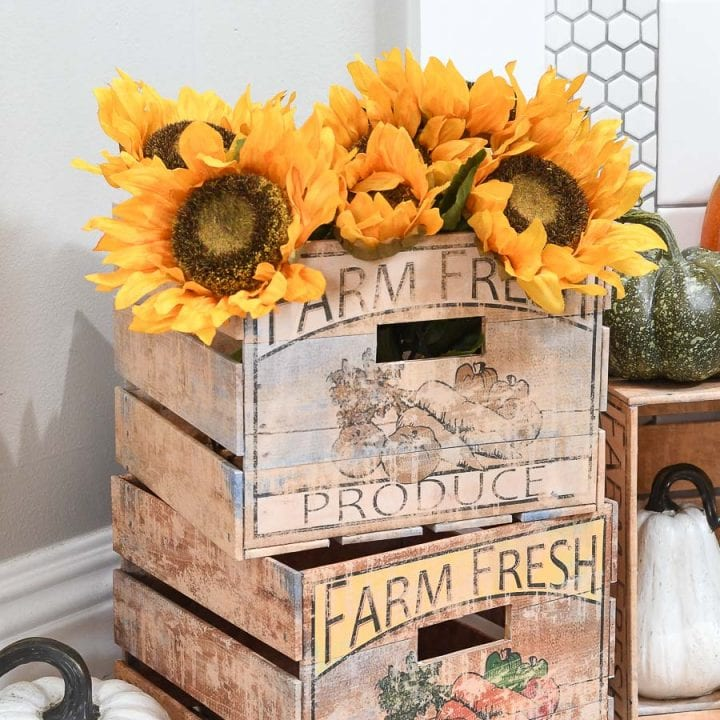 Two DIY crates with a farm fresh label on the front holding sunflowers and pumpkins.