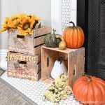 Three DIY crates in front of the fireplaces displaying pumpkins and sunflowers.