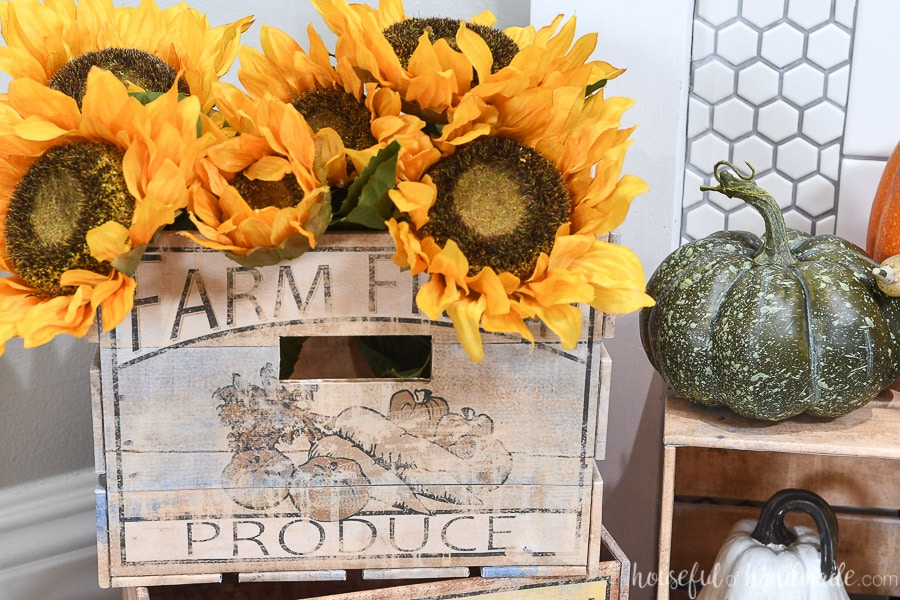 Close up of the light crate with worn-out black and white label on the front holding sunflowers.