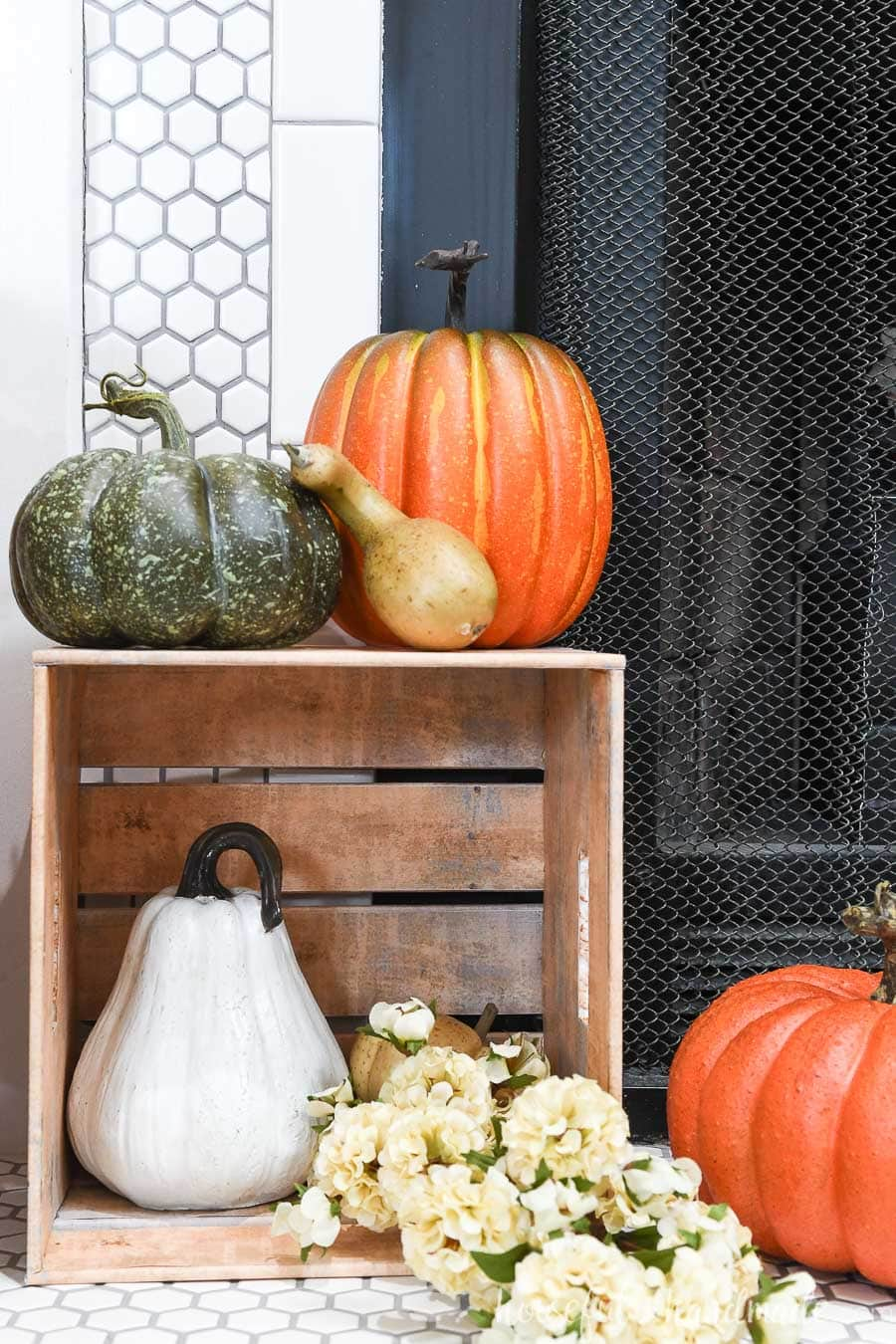 Paper crate on it's side displaying pumpkins and gourds in front of a fireplace.