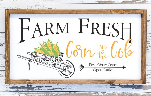 Wood sign with vintage wheelbarrow full of corn for fall.