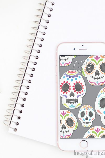 Smartphone with sugar skulls on a gray digital background sitting on a notebook.