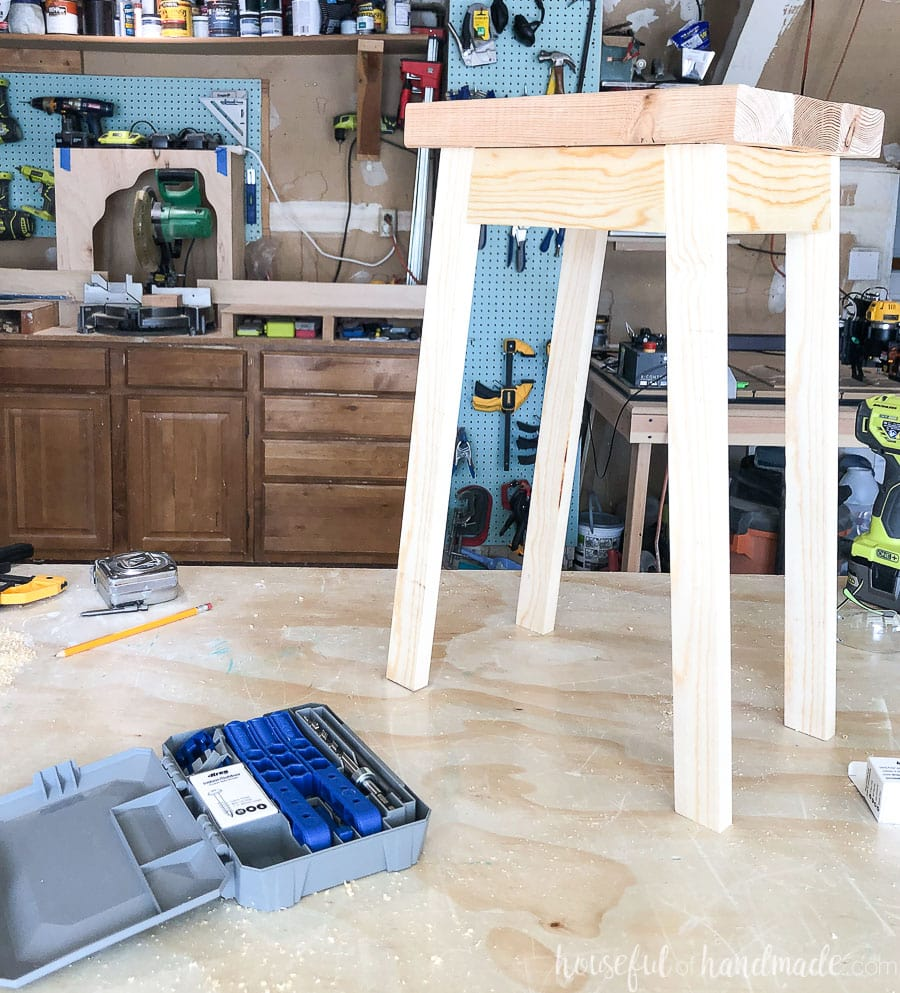 Garage workshop table with finished plant stand on it next to the Kreg 320 pocket hole jig.