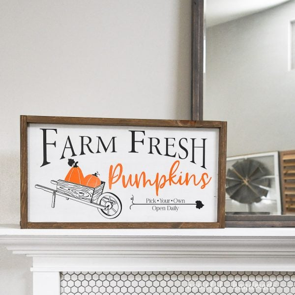 Fall wood sign with pumpkin patch vinyl design on it sitting on a mantel.