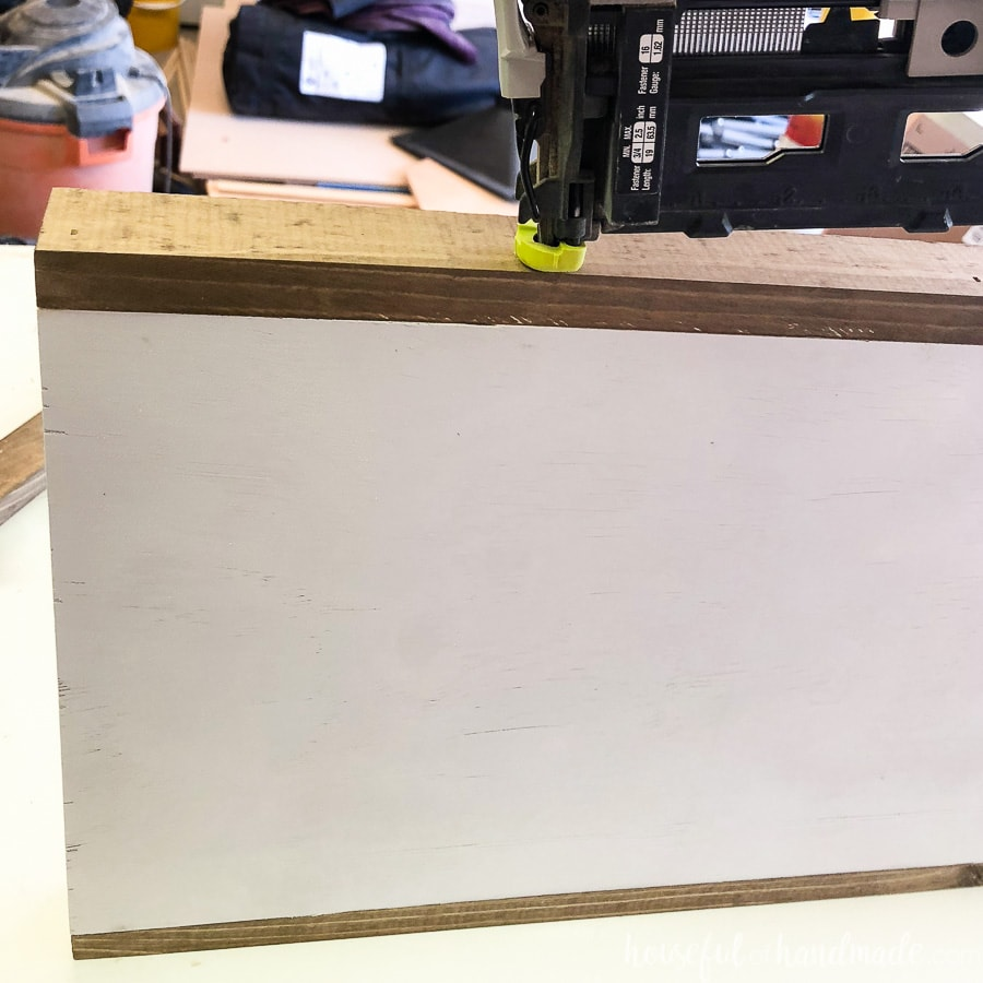 Attaching the long frame sides of the wood sign to the plywood.