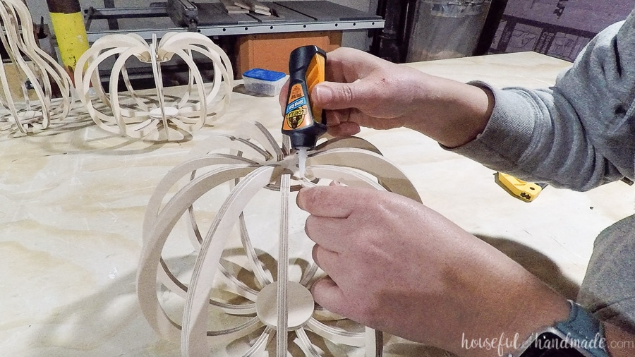 Glueing the bottom of the wood pumpkin pieces to the bottom circle.