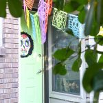 Colorful Day of the Dead paper banners hanging from the trees in front of a green door with a Sugar Skull wreath on it.