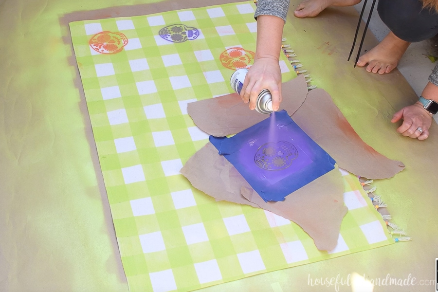 Painting a purple sugar skull on the drop cloth mat with spray paint and a stencil.