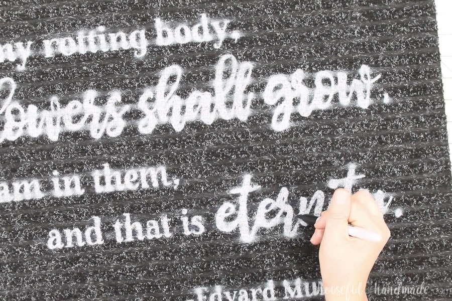 Using a Sharpie to remove any paint overspray on the ribbed doormat.