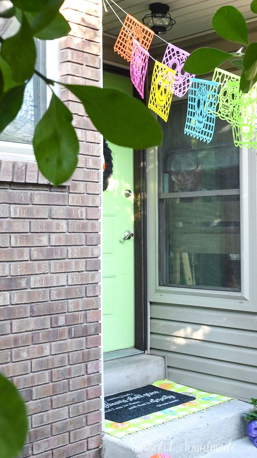 Small porch with bight green door and Day of the Dead layered doormat on it.