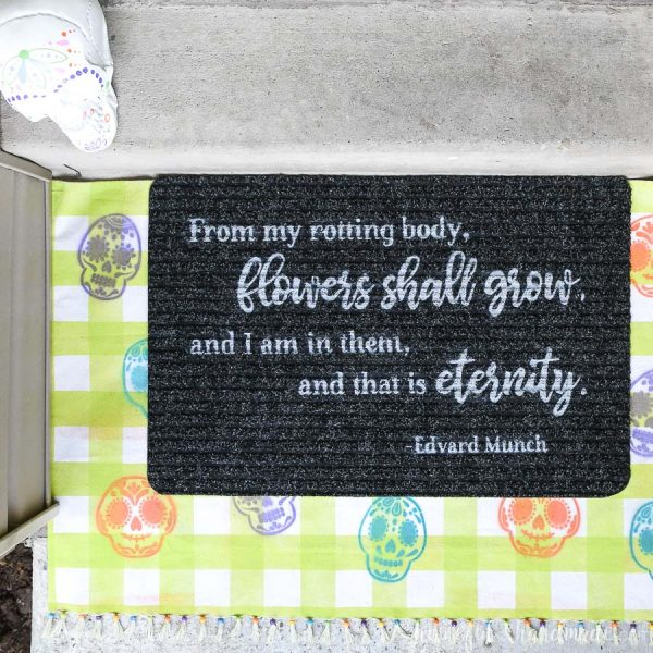 Closup of the DIY Halloween layered doormat with sugar skulls and a Day of the Dead quote.