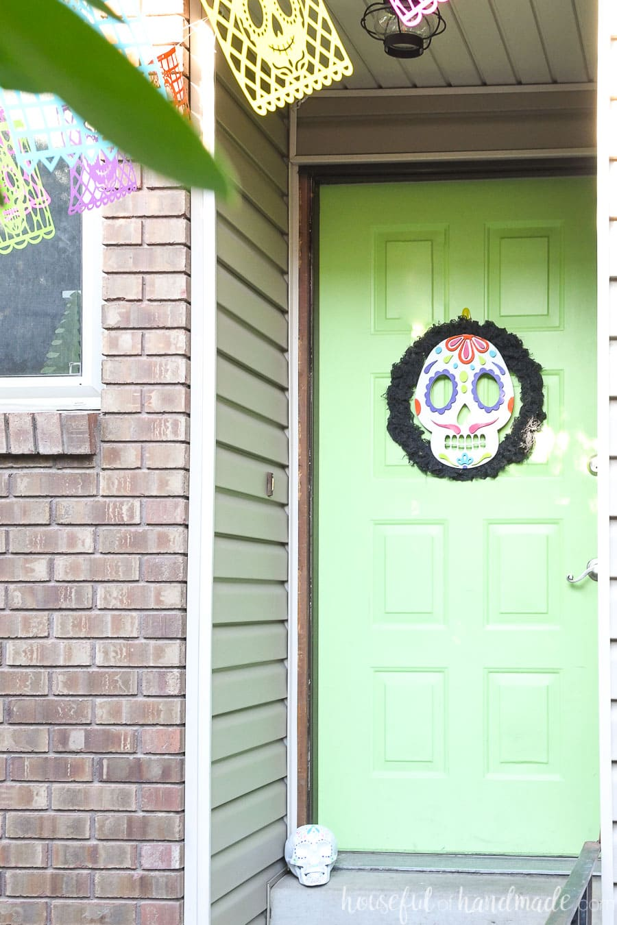 Front entry with a door decorated for Halloween in Day of the Dead theme.