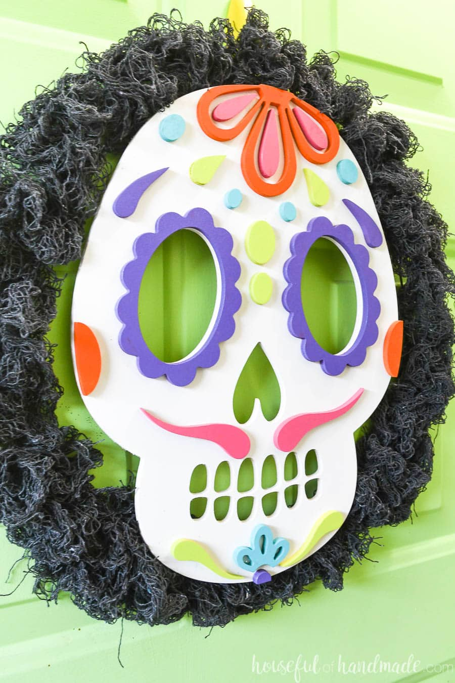Close-up view of the completed DIY sugar skull wreath hanging on the front door.