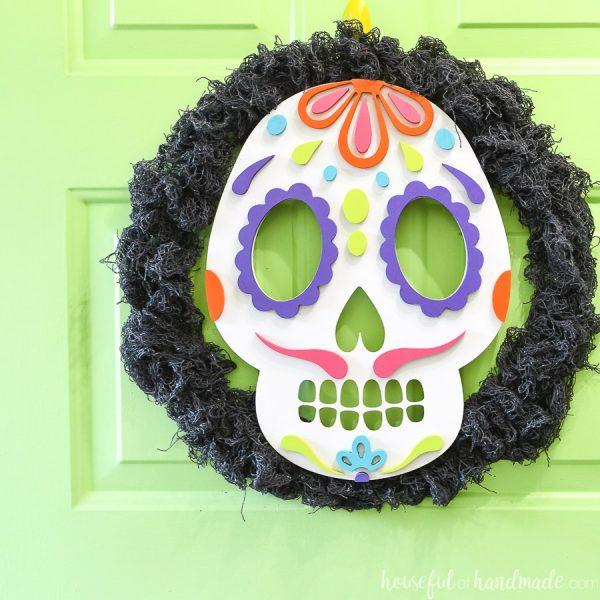 Green door with sugar skull wreath hanging on it.
