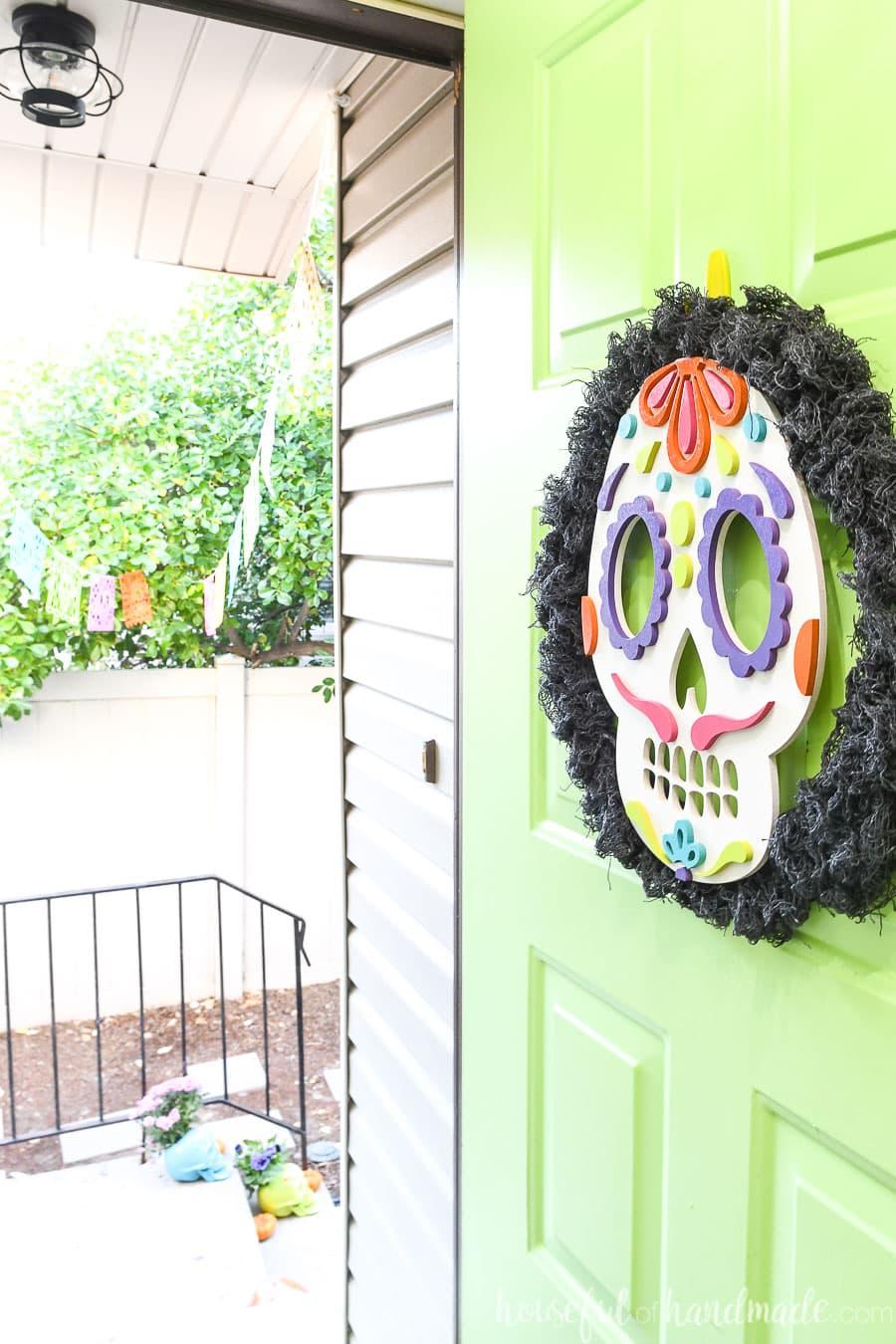 Front door open with sugar skulls wreath hanging on it.