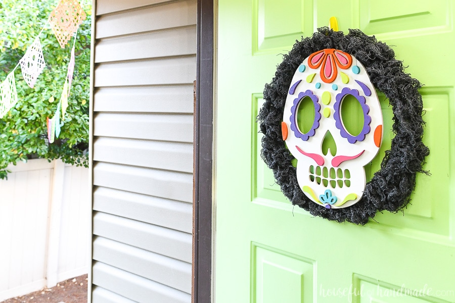 Horizontal view of the green front door open with a sugar skull wreath hanging on it.