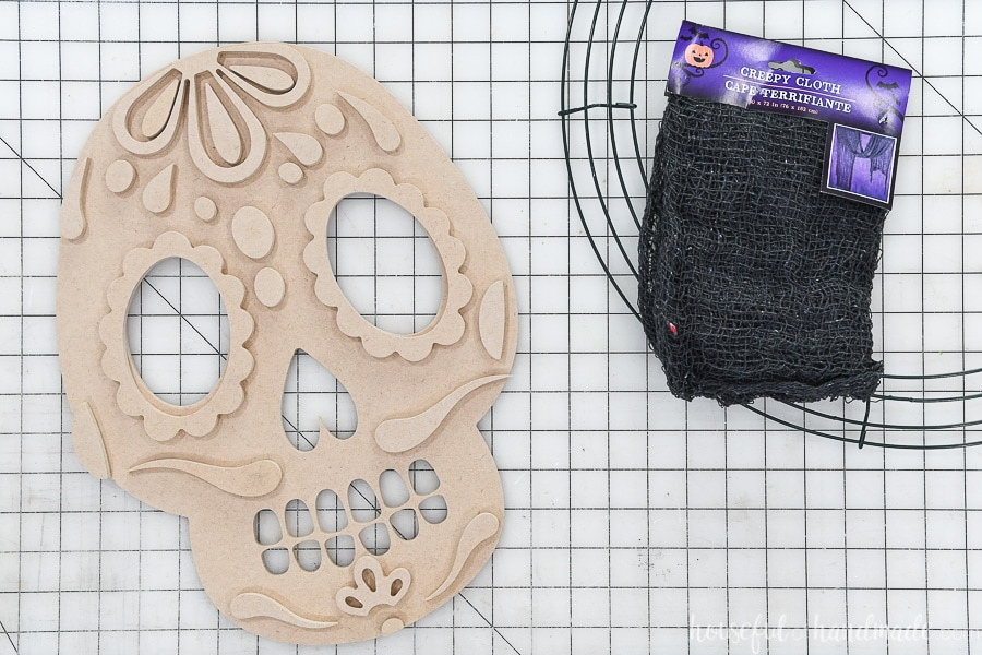 Sugar skull design cut out of MDF next to wire wreath frame and creepy cloth.