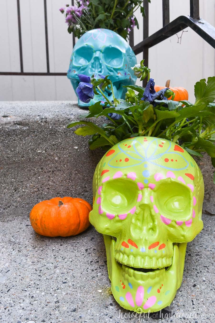 Green and blue sugar skull planters holding fall flowers on a porch.