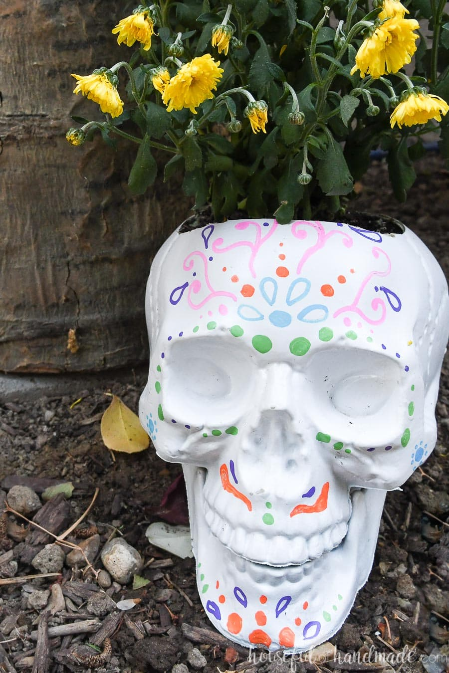 White DIY sugar skull pot with yellow mums planted in them.