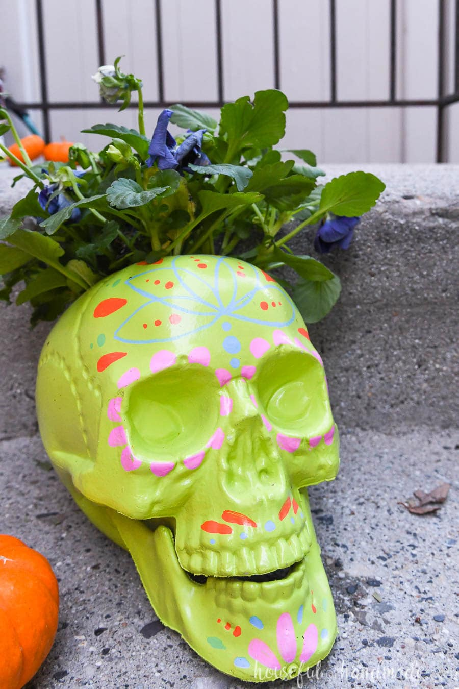 Lime green sugar skull planter with colorful decorations around the face.