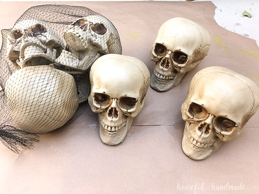 Three plastic skulls in a bag and three more outside of the bag on brown paper.