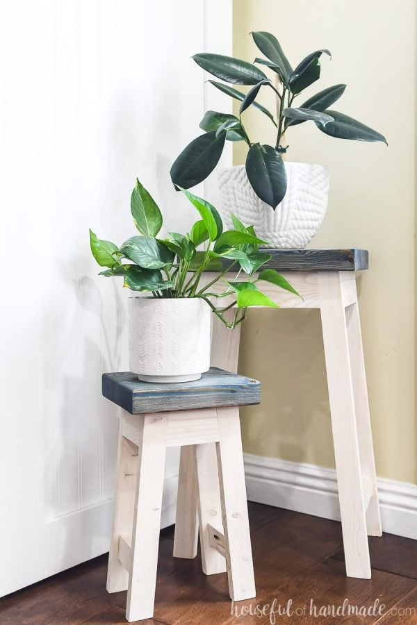DIY nesting plant stands holding a rubber plant and pothos plant in white pots.