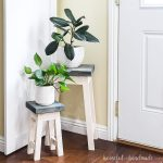 Nesting plant stands with navy stained tops holding plants in the corner.