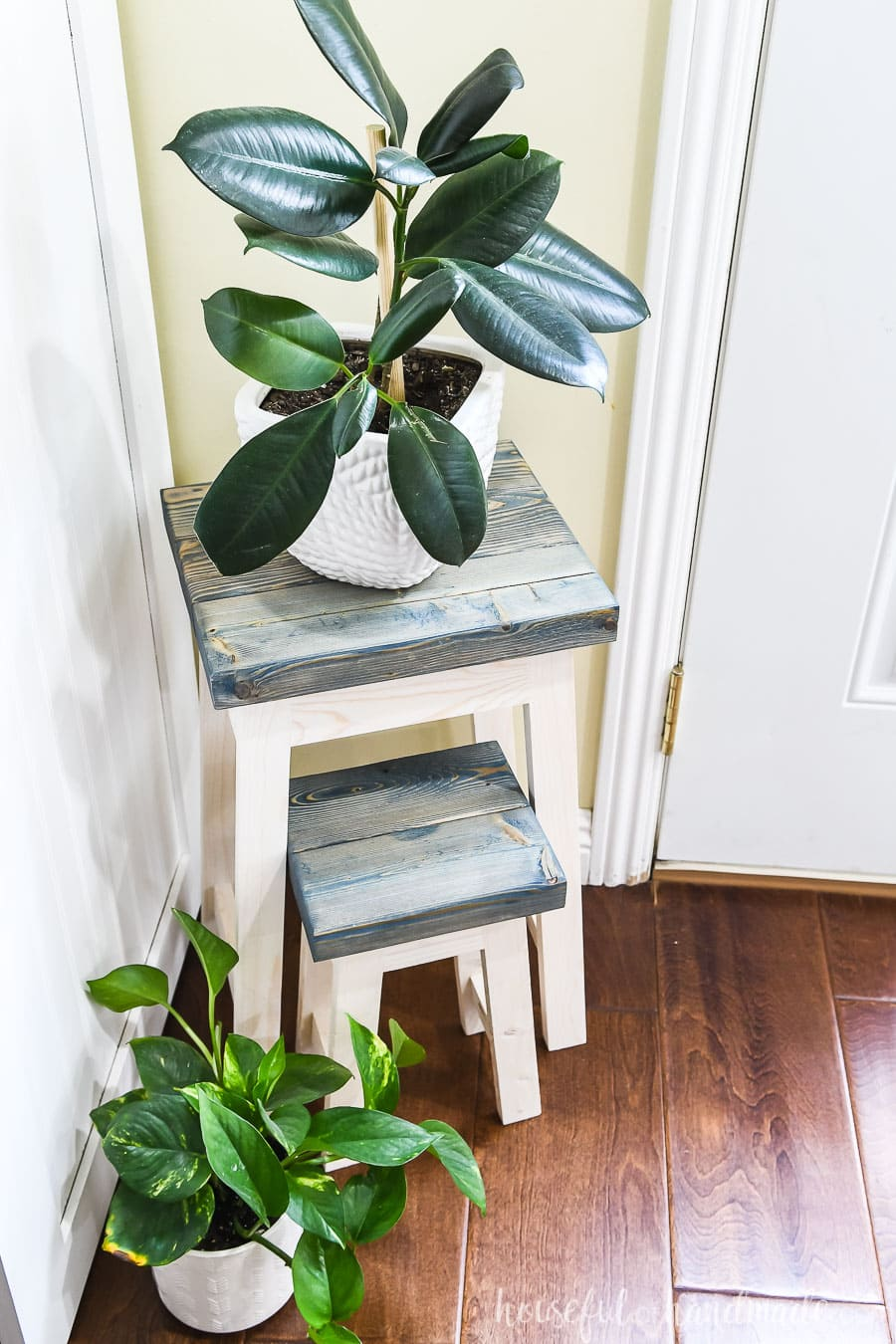 Two plant stands in the corner with the small one nesting under the larger one.