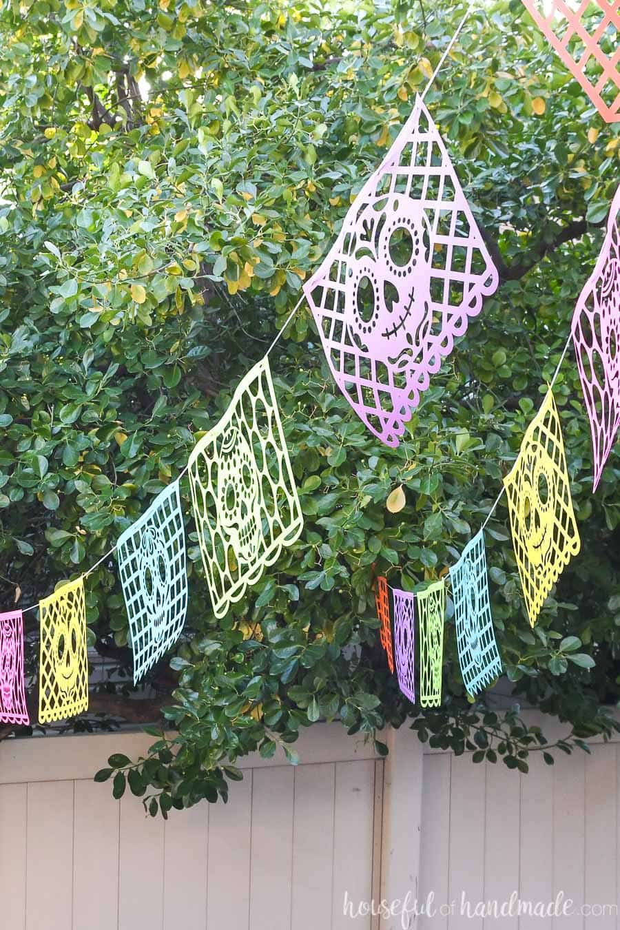 Picture of colorful halloween paper banners hanging outside with sugar skull designs on them.
