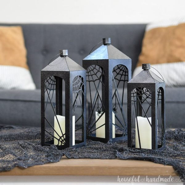 Three paper Halloween lanterns on a table with black creepy cloth.