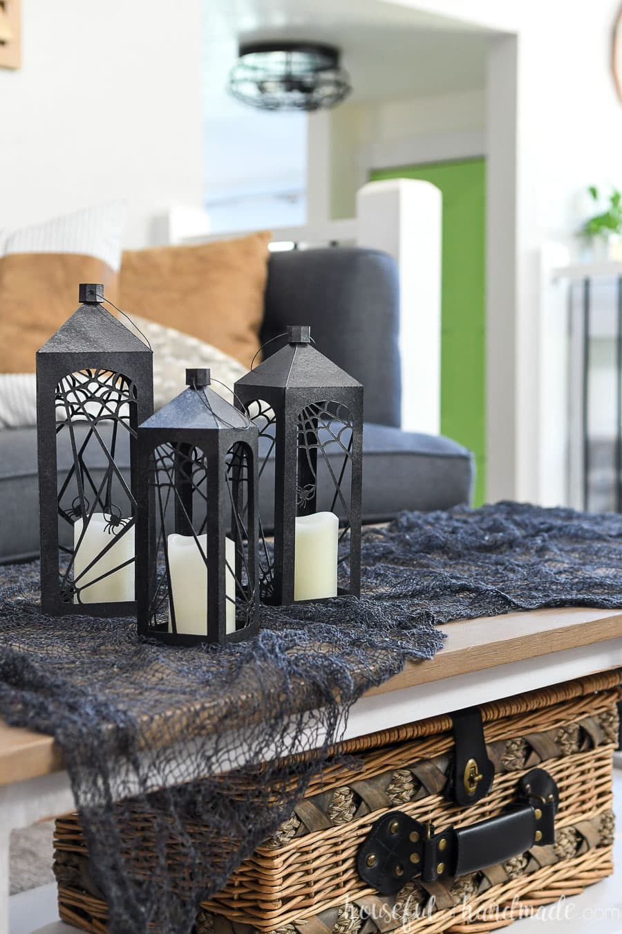 Three black Halloween lanterns on a table with candles inside.