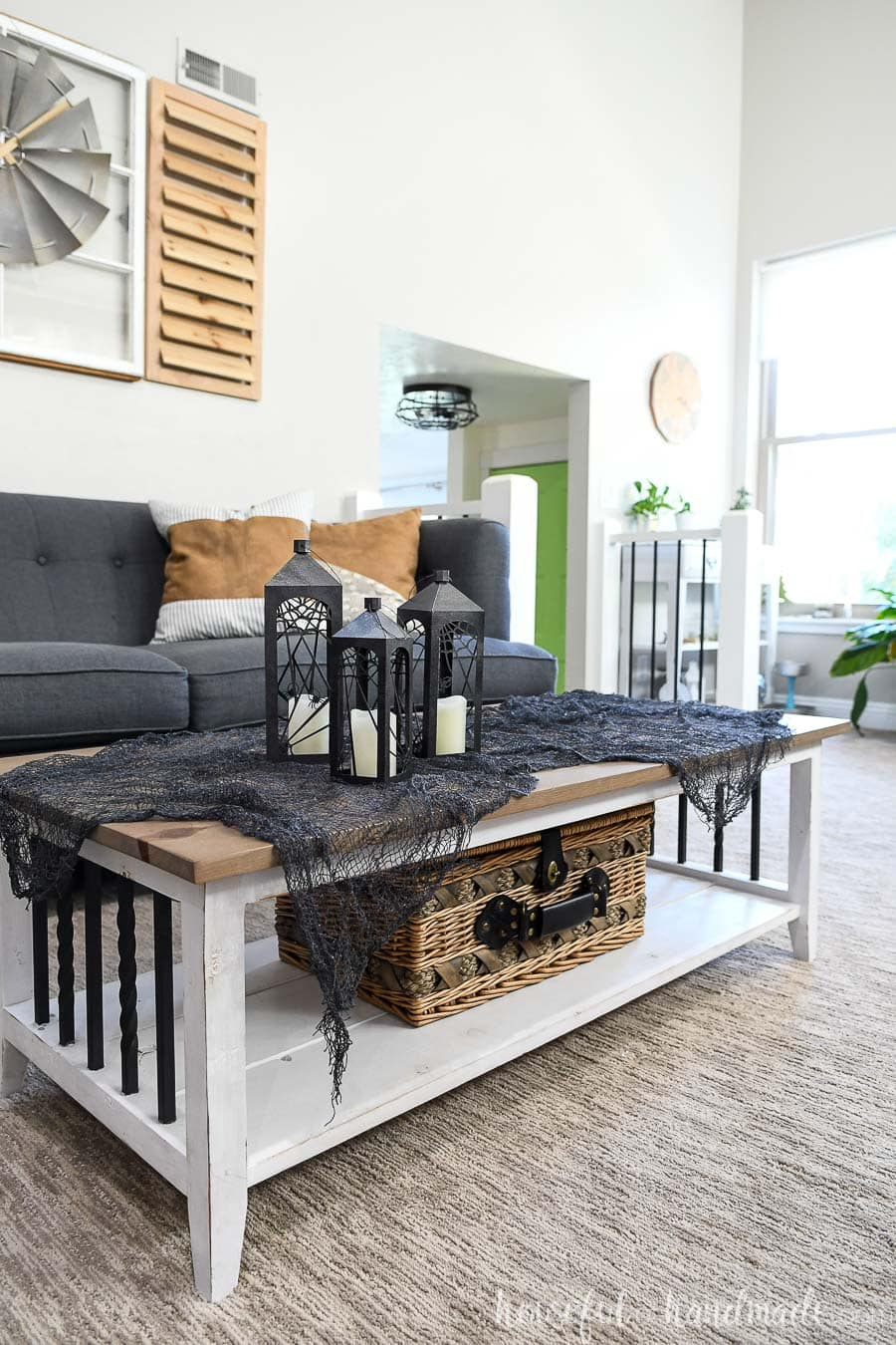 Living room with farmhouse coffee table and glamorous Halloween decorations on it.