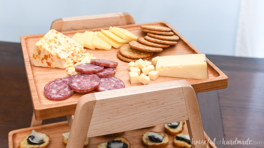 Close up of the top serving tray holding cheeses and crackers on the tiered serving tray.
