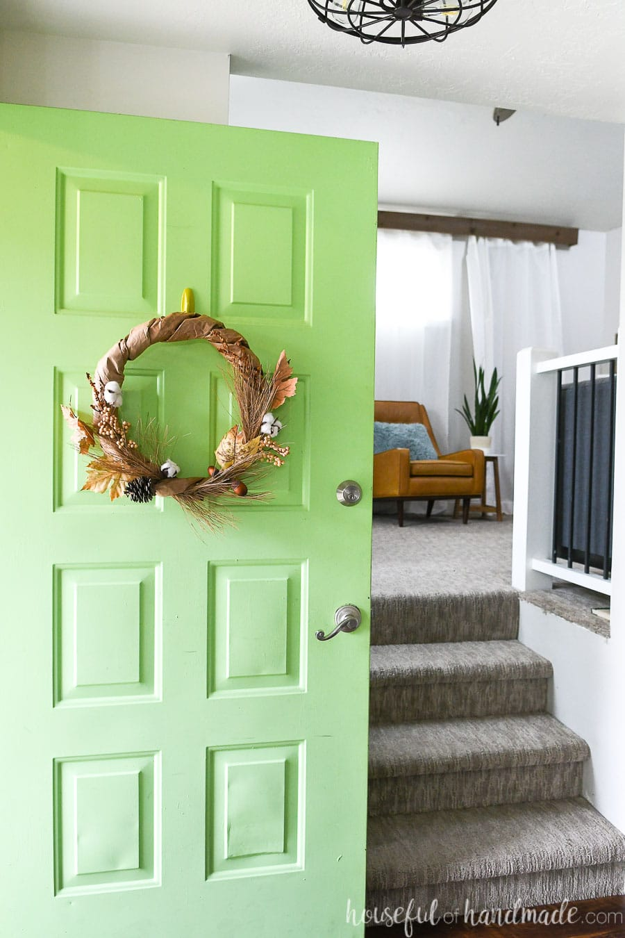 Entryway with green door open and a rustic fall wreath hanging on the door.