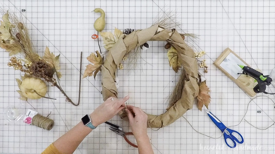 Tying a piece of jute twine to the back of the fall wreath to hang.