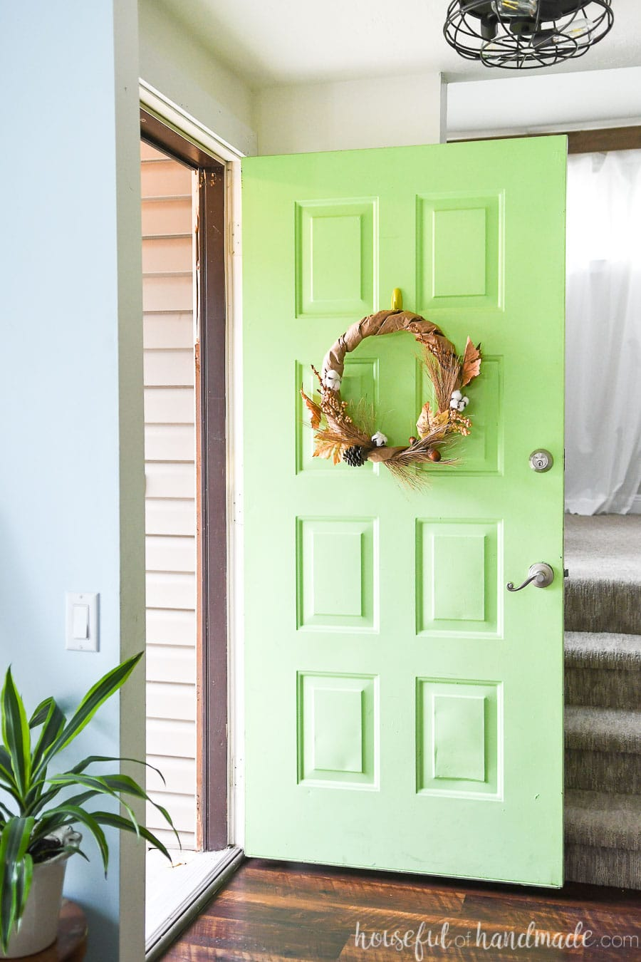 Green front door opened up showing the DIY upcycled wreath for fall hanging on it.