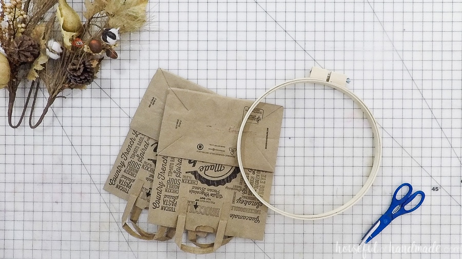 Two paper grocery bags and an embroider hoop on the craft table.