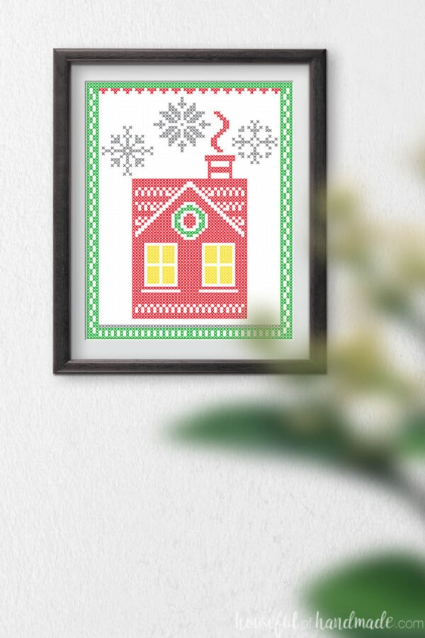 Printable Christmas art that looks like a Nordic Christmas house with cross-stitch snowflakes.