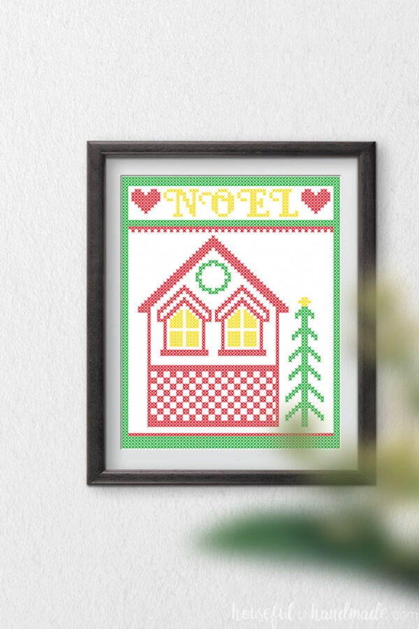 Cross-stitch house with a frame and Noel around it as printable Christmas art.