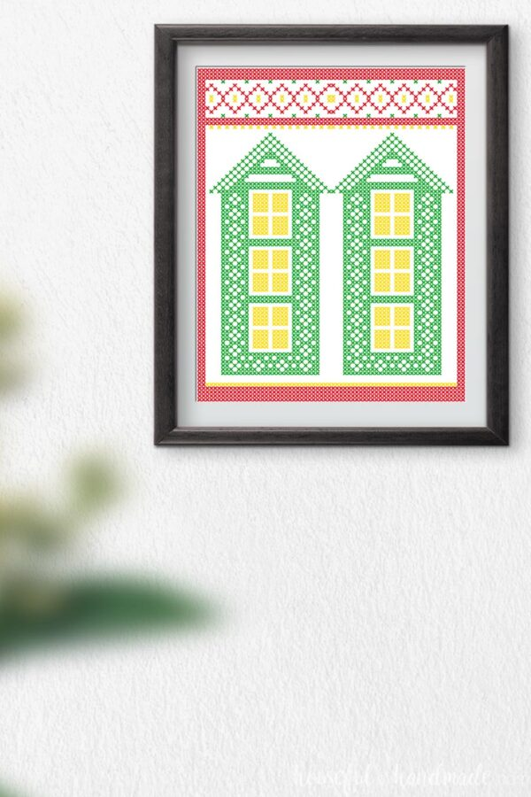 Cross-stitched printable art with two tall green houses and a Christmas border.