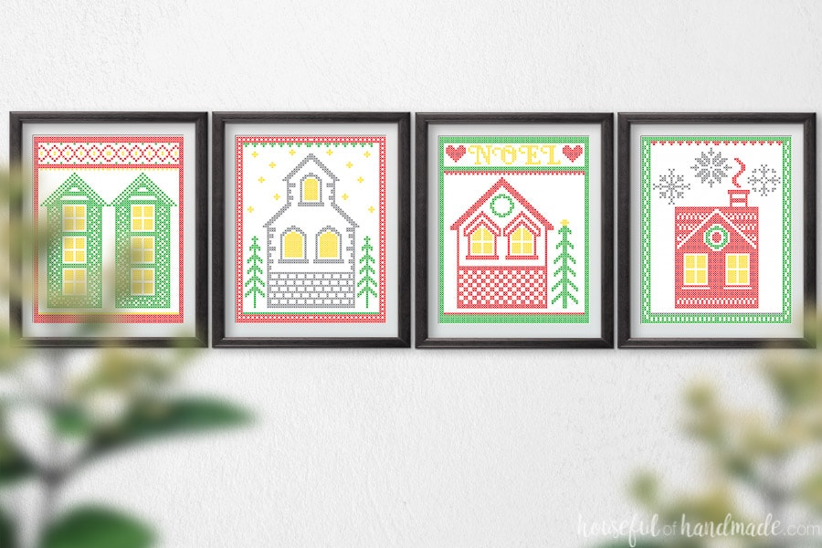 Four cross-stitched village printable art pieces in frames on a wall.