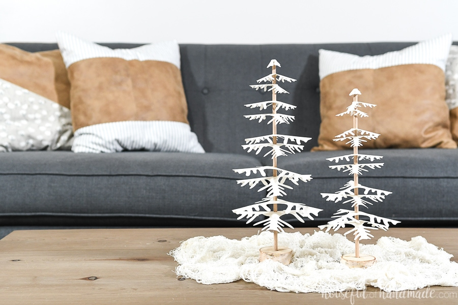 Two handmade decorative Christmas trees on the coffee table with white branches.