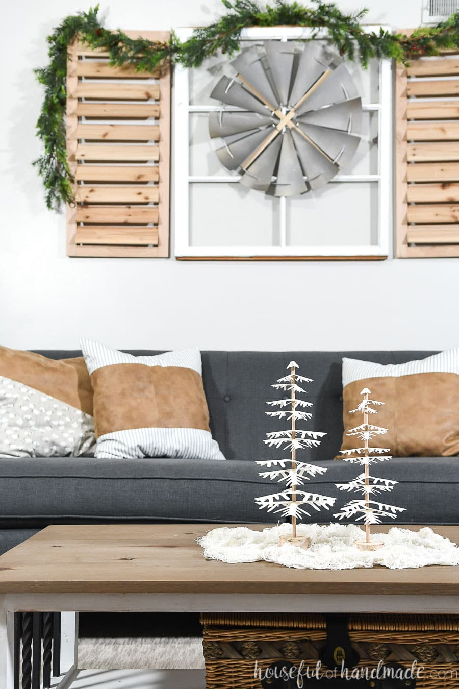 Living room decorated with white tabletop paper Christmas trees on the coffee table in front of the sofa.