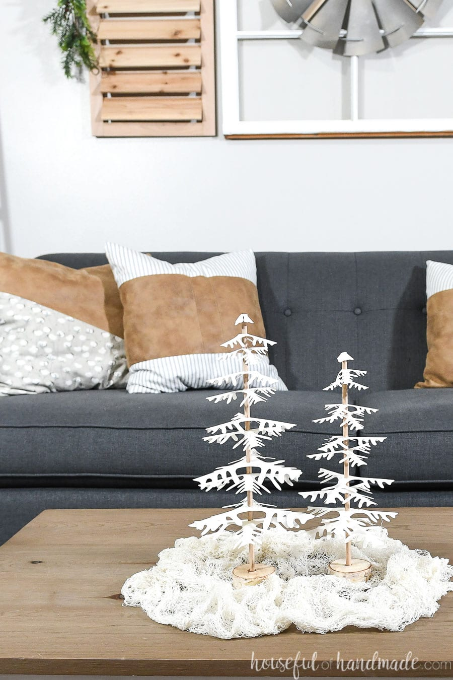 Coffee table decorated for Christmas with white DIY decorative Christmas trees.