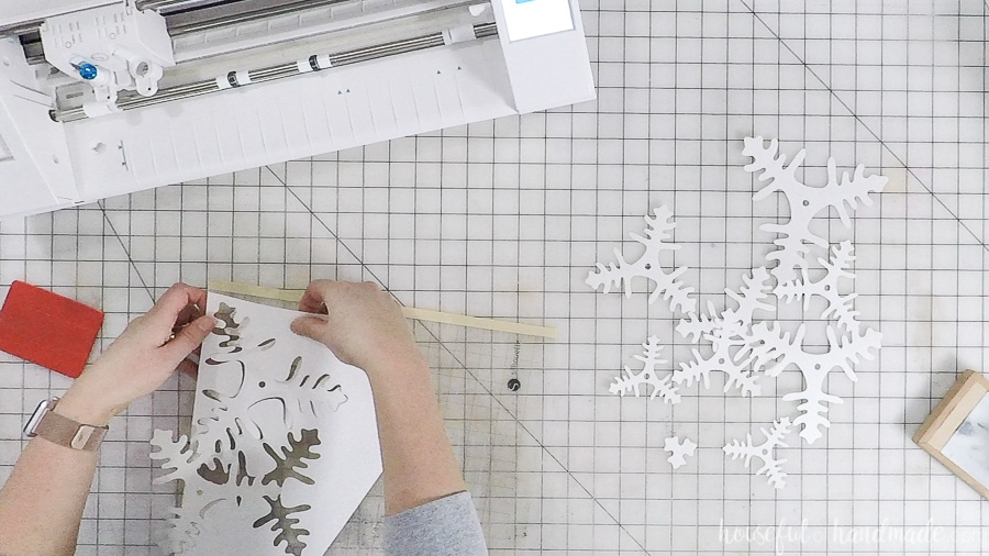 Decorative paper Christmas tree branches cut out of white glitter cardstock with a Silhouette Cameo.