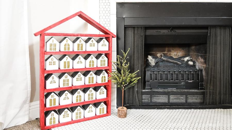 Wood house shaped shelf used as part of the modern Christmas advent calendar.