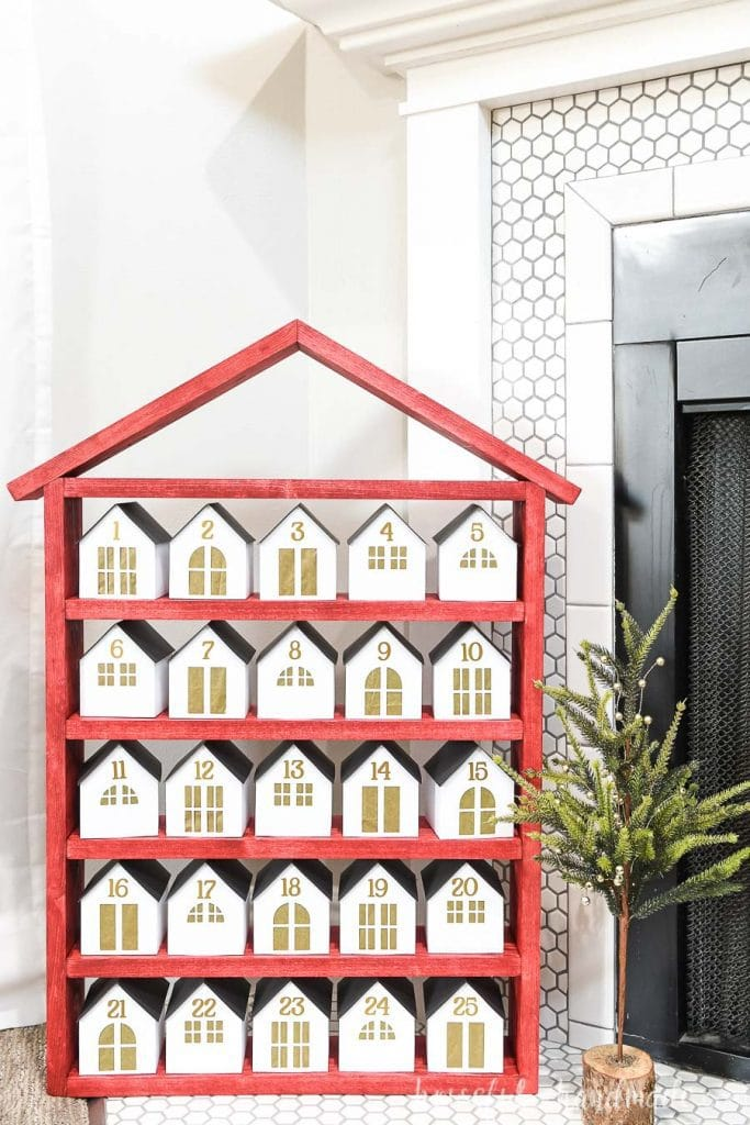 Red shelves with 25 white & gold paper houses on them to open each day in December until Christmas.
