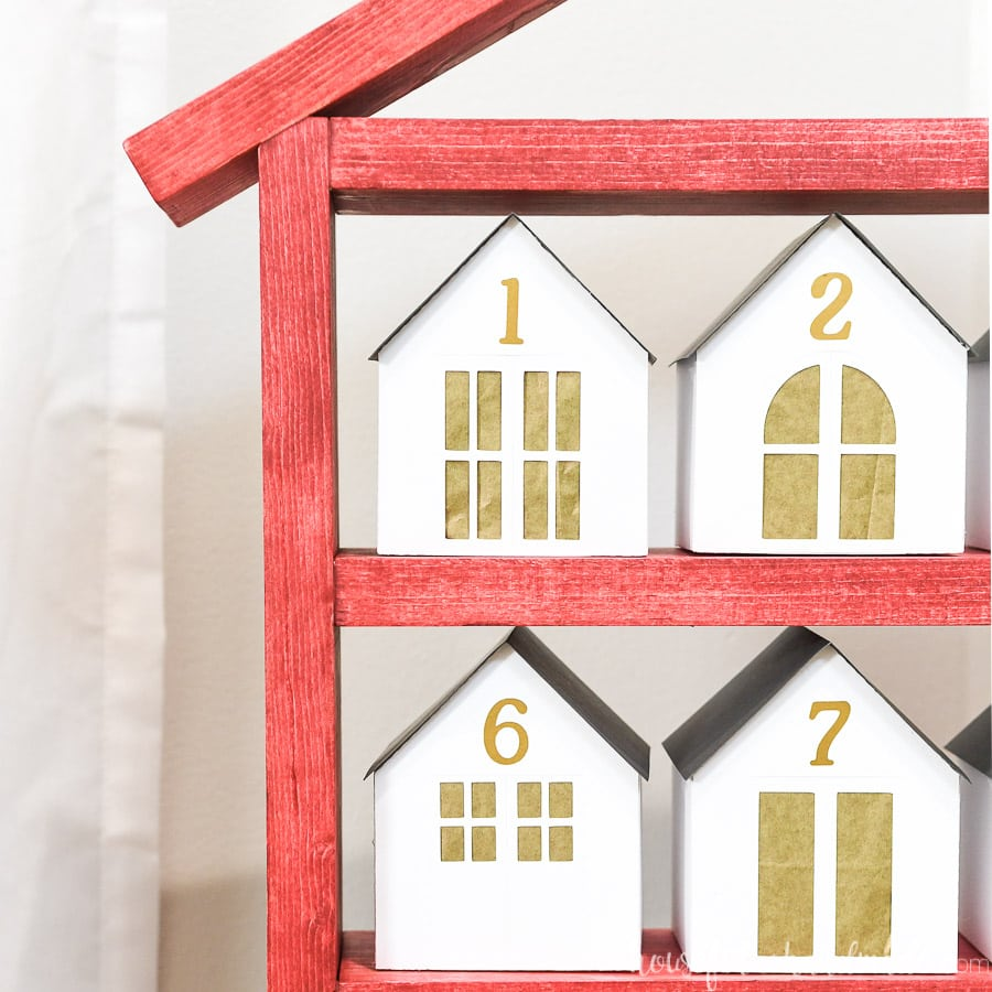 Close-up of the wooden house shaped shelves with paper houses on it.