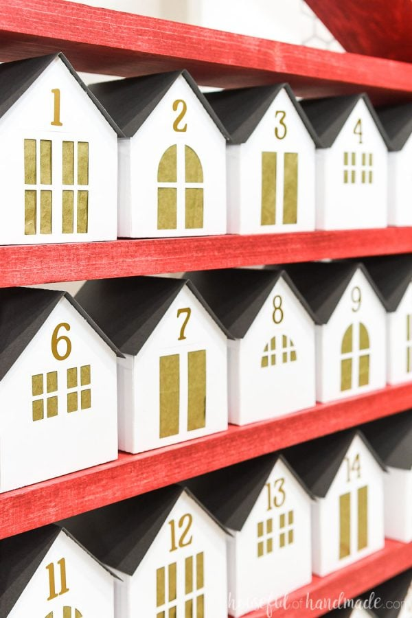 Close up angled shot of the paper houses on the DIY advent calendar with gold tissue paper covering the openings.
